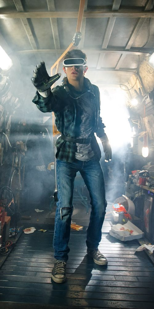 In his dystopian home, the main character of Ready Player One wears a virtual reality headset and reaches towards the virtual world.