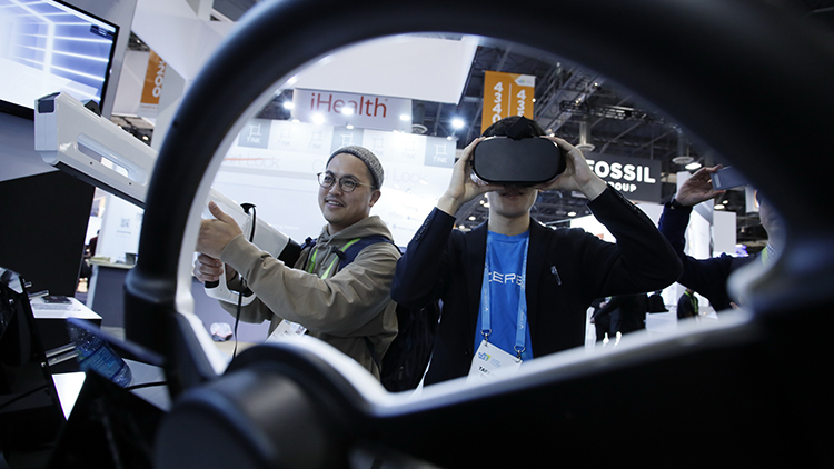 A man wears a virtual reality headset at a busy tradeshow